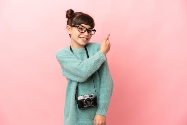 Niña fotógrafa aislada sobre fondo rosa apuntando hacia atrás