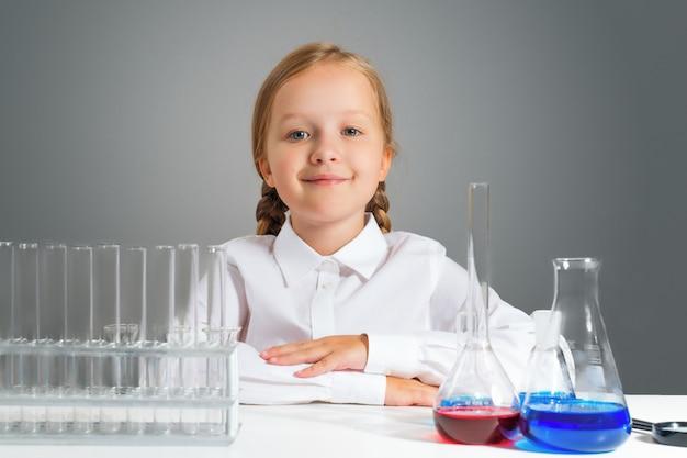 Niña con frascos para química se sienta en una mesa.