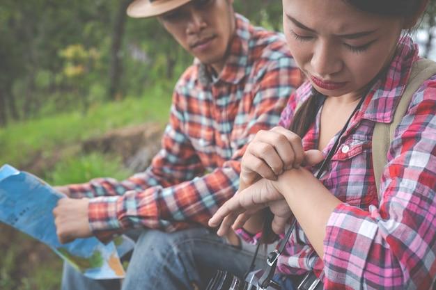 La niña fue mordida por un insecto en el dorso de la mano en una colina en un bosque tropical, caminando, viajando, escalando.