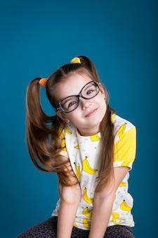 Niña con gafas y camiseta de plátano sobre fondo azul