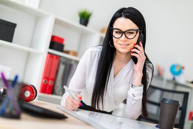 Una niña con gafas se para cerca de una mesa, habla por teléfono y dibuja un marcador en una pizarra magnética.