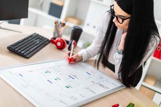 Una niña con gafas se para cerca de la mesa, sostiene un marcador en la mano y dibuja en un tablero magnético.