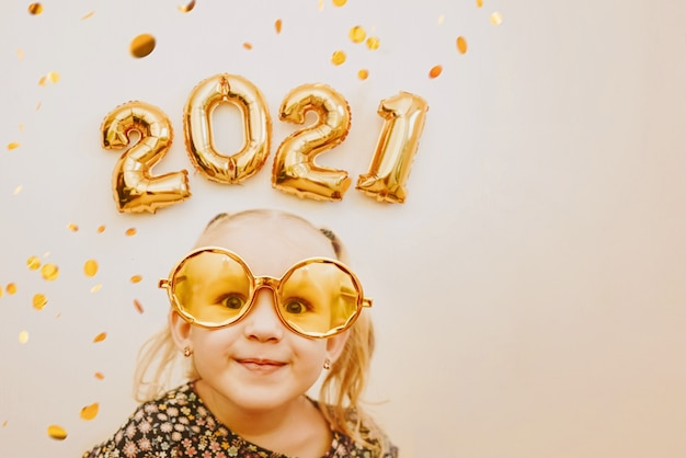 Niña con gafas de mascarada de oro sonriendo, bromeando. feliz 2021