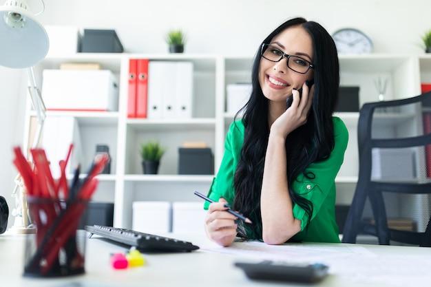 Niña con gafas en la oficina habla por teléfono, sostiene un lápiz en la mano y sonríe.