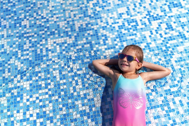 Niña con gafas de sol y sombrero con unicornio en la piscina al aire libre del complejo de lujo en vacaciones de verano en la isla de playa tropical