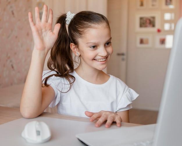 Niña con ganas de responder una pregunta sobre lecciones en línea