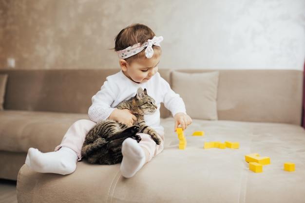 Niña con gatito atigrado sentado en el sofá y juega con cubos amarillos
