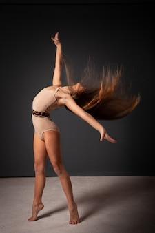 Una niña gimnasta en el estudio sobre un gris.