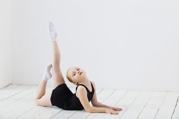 Niña gimnasta haciendo estiramientos en una habitación luminosa en un lindo y feliz