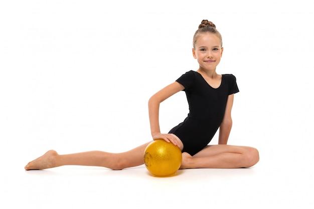 Niña gimnasta en trico negro de altura completa se sienta en media página con una pelota amarilla