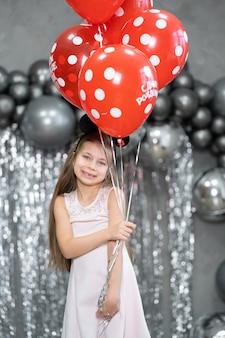 Niña con globos celebra su cumpleaños