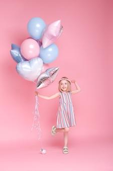 Niña con globos sobre una superficie rosa