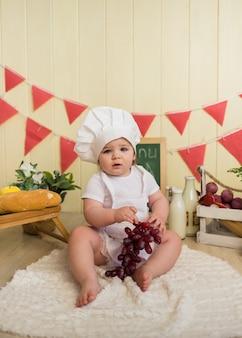 Niña con gorra blanca y delantal se sienta sosteniendo uvas