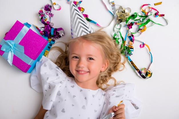Niña con gorra de cumpleaños sonriendo con caja de regalo y confeti