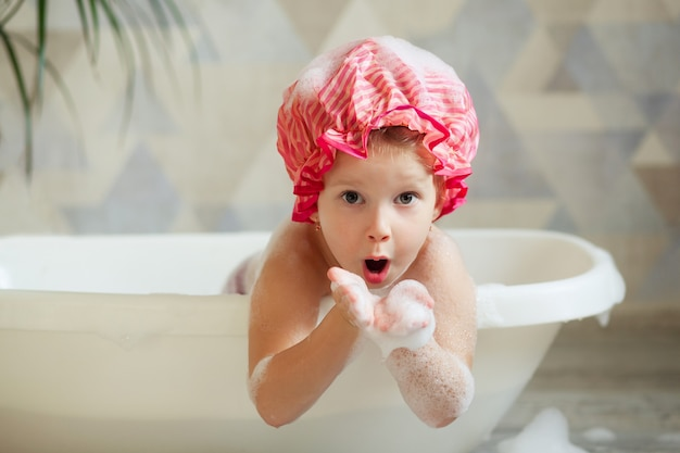Niña con gorra rosa, tomando un baño de burbujas