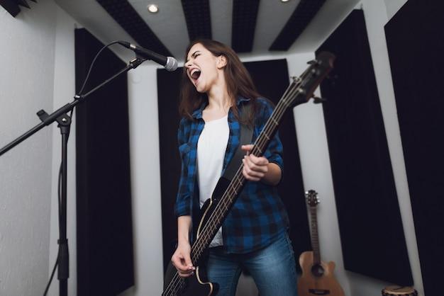 La niña está grabando una canción en un estudio de grabación moderno.