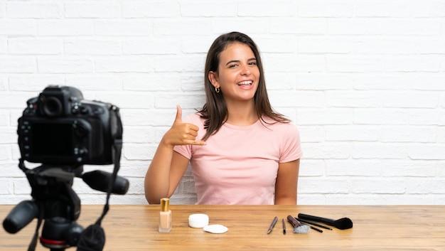 Niña grabando un video tutorial haciendo gestos telefónicos