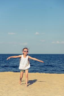 Niña graciosa en gafas de sol está corriendo y sonriendo.
