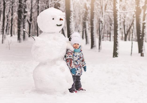 Niña y un gran muñeco de nieve de invierno en el parque