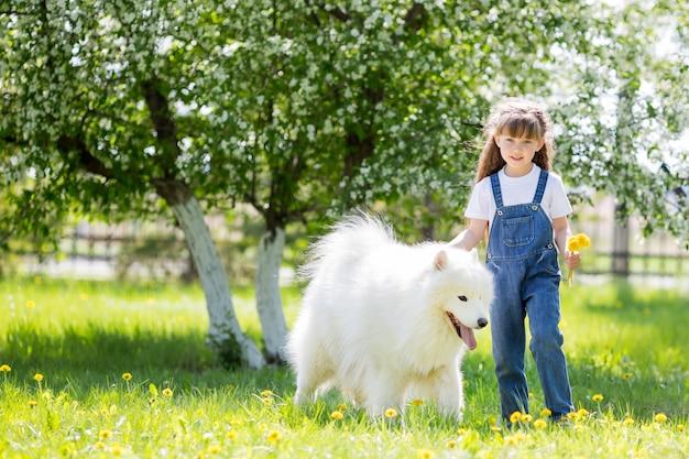 Niña con un gran perro blanco en el parque.