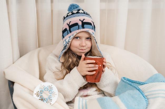 Niña con gran taza de té caliente en gorro de punto caliente bajo una manta de lana