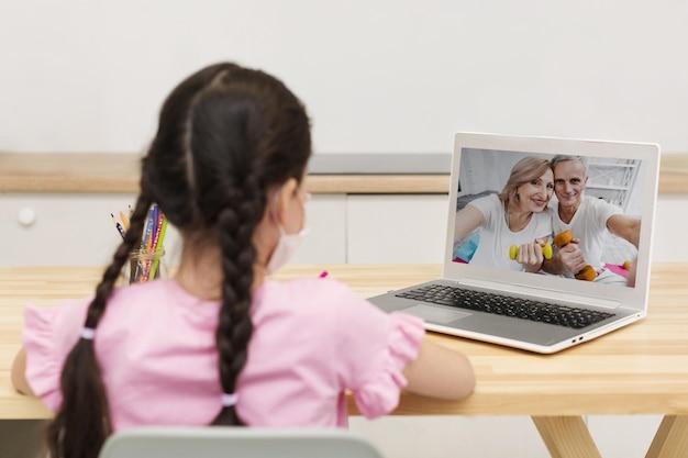 Niña hablando con sus padres en plataformas en línea