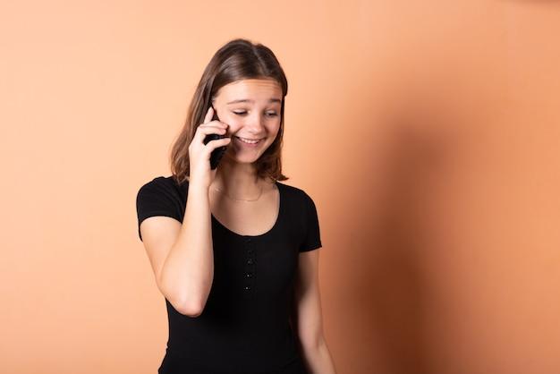 La niña está hablando por teléfono con sorpresa, sobre un fondo naranja claro. para cualquier propósito.