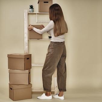 La niña hace cajas de papel en un estante de madera. almacenamiento y embalaje ecológicos.