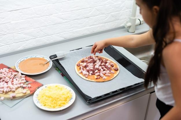 Niña hace pizza en casa