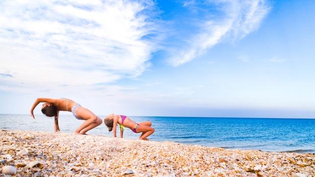 Una niña hace un puente con una pierna levantada y su hermana la ayuda