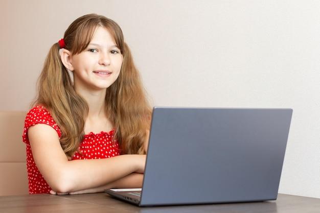 Niña haciendo los deberes en el portátil en casa