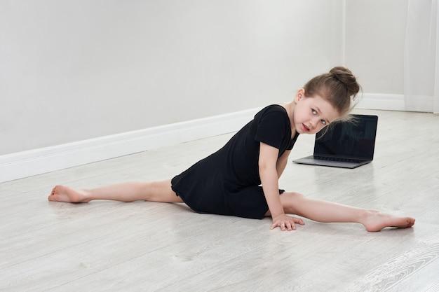 Niña haciendo ejercicios de gimnasia en casa utilizando aprendizaje en línea con computadora portátil, concepto de educación en internet