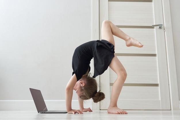 Niña haciendo ejercicios de gimnasia en casa utilizando aprendizaje en línea con computadora portátil