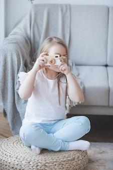 Niña haciendo una foto. linda fotografía de interior. adorable niño jugando con la cámara.
