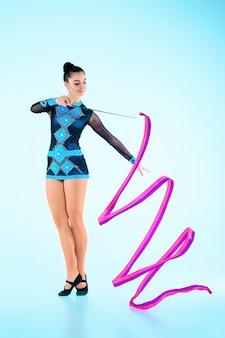La niña haciendo gimnasia baila con cinta de colores sobre un fondo azul.