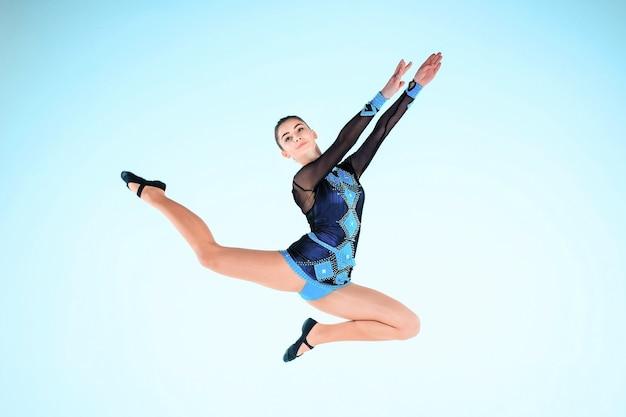 La niña haciendo gimnasia baila sobre un fondo azul.