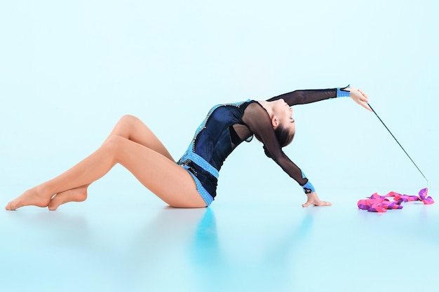 La niña haciendo gimnasia danza con cinta de color sobre un fondo azul.