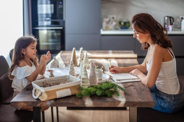 La niña está haciendo manualidades de cono de árbol de navidad y decorando con botón, hilo mientras su madre escribe texto en el teléfono y el gato camina debajo de la mesa de la cocina. preparación de la fiesta de navidad y año nuevo