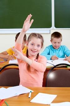 Niña haciendo una pregunta a la maestra