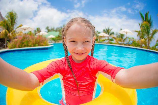 Niña haciendo selfie en anillo de goma inflable en la piscina