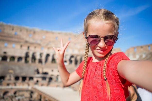 Niña haciendo selfie en coliseo, roma, italia. retrato de niño en lugares famosos de europa