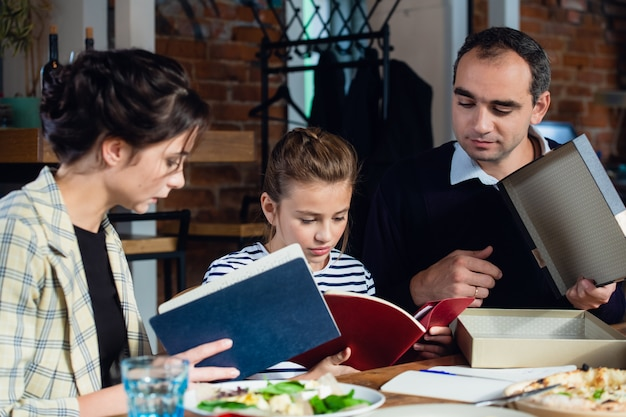 Una niña haciendo su tarea en la mesa de la cocina con sus padres cerca