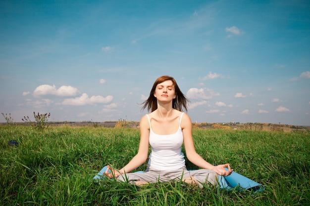 Niña haciendo yoga pose de loto en el parque sobre el cielo azul