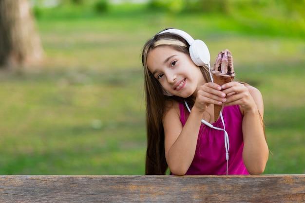 Niña con helado de chocolate y auriculares