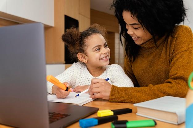 Niña y hermana mayor en casa durante la escuela en línea