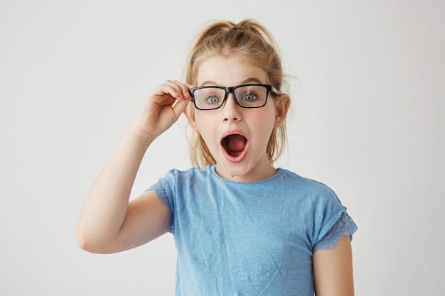 Niña hermosa con brillantes ojos azules y cabello rubio posando con la boca abierta, sosteniendo sus gafas con la mano mirando súper sorprendida.