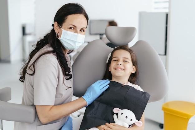 Niña hermosa en el dentista mirando y sonriendo