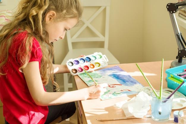 Niña hermosa pintura con acuarelas, sentado en su casa a la mesa
