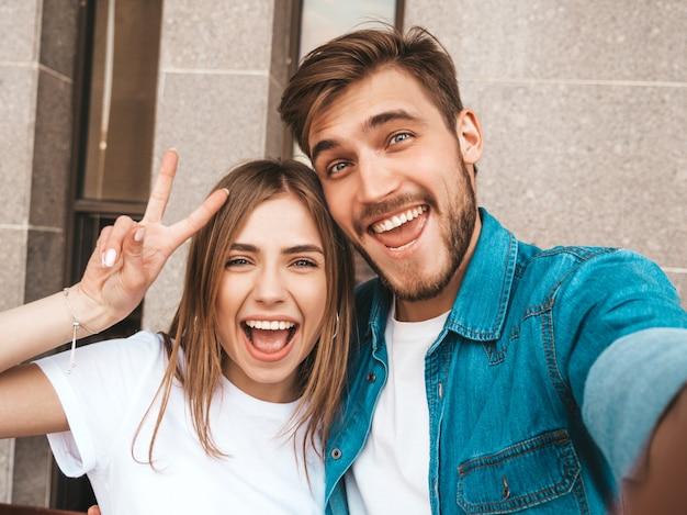 Niña hermosa sonriente y su novio guapo en ropa casual de verano. familia feliz tomando selfie autorretrato de sí mismos en la cámara del teléfono inteligente. muestra signo de paz y guiñando un ojo en la calle