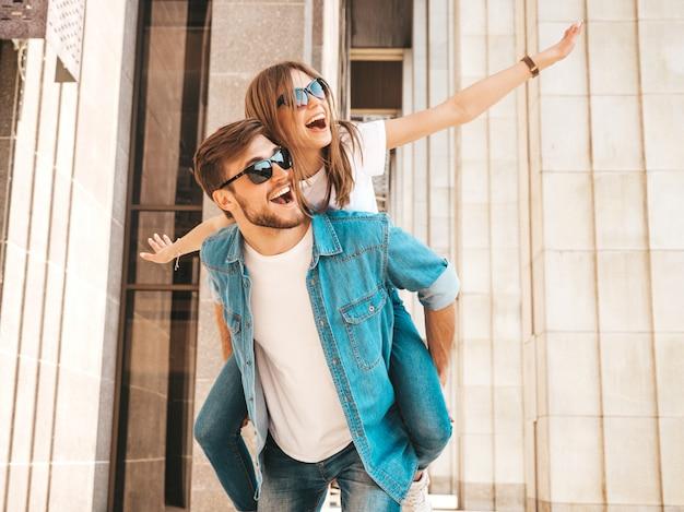 Niña hermosa sonriente y su novio guapo en ropa casual de verano. hombre con su novia en la espalda y ella levantando las manos.